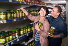 Portrait de sélectionner plus âgé de couples conserves au vinaigre à l'épicerie Photographie stock