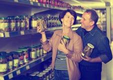 Portrait de sélectionner plus âgé de couples conserves au vinaigre à l'épicerie Image stock