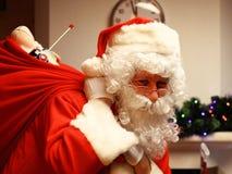 Portrait de sac heureux à participation de Santa Claus avec des cadeaux et de regarder l'appareil-photo Photos stock