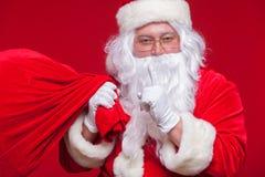 Portrait de Santa Claus avec le sac rouge énorme gardant l'index par sa bouche et regardant l'appareil-photo Photos stock