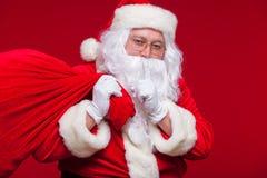 Portrait de Santa Claus avec le sac rouge énorme gardant l'index par sa bouche et regardant l'appareil-photo Photo libre de droits