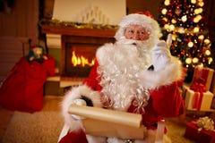 Portrait de Santa Claus heureuse avec le list d'envie Images stock