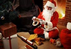 Portrait de Santa Claus heureuse se reposant à sa pièce à la maison Photos stock