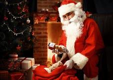 Portrait de Santa Claus heureuse se reposant à sa pièce à la maison Photographie stock