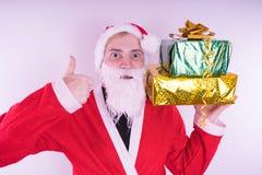 Portrait de Santa Claus mince avec des cadeaux de Noël Santa Claus heureuse juge des boîte-cadeau d'isolement sur le fond blanc S photographie stock libre de droits