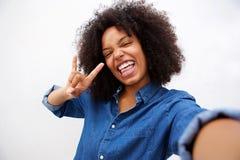 Portrait de Selfie de femme heureuse faisant le geste de main de rock photo libre de droits