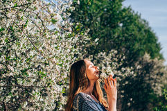 Portrait de sentir un bouquet de jeune fille de fleurs dans la cerise g Photos stock