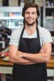 Portrait de serveur de sourire se tenant avec le bras croisé Image stock