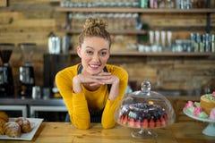 Portrait de serveuse de sourire se penchant au compteur Photos libres de droits