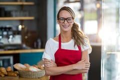 Portrait de serveuse de sourire se tenant avec des bras croisés Photos libres de droits