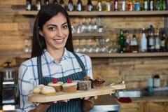 Portrait de serveuse de sourire tenant des petits gâteaux dans le plateau en bois au compteur photo libre de droits