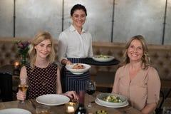 Portrait de serveuse et de clients heureux à la table de salle à manger Images stock