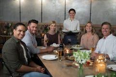 Portrait de serveuse et de clients heureux à la table de salle à manger Photos libres de droits