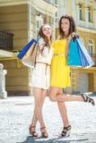 Portrait de shopaholics Deux amies tenant les paniers a Image stock