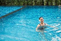Portrait de sourire de belle femme dans la piscine, beau y Photos stock
