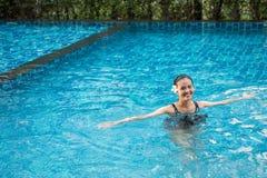 Portrait de sourire de belle femme dans la piscine, beau y Photos libres de droits