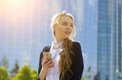Portrait de sourire d'étudiant féminin dehors Téléphone européen blond de participation de fille B?timent moderne sur le fond images stock