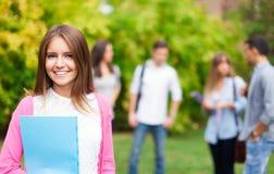 Portrait de sourire d'étudiant lisant un livre Photos stock