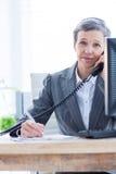 Portrait de sourire d'une femme d'affaires téléphonant et inscription Photos stock