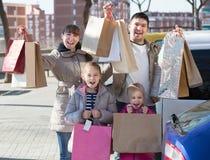 Portrait de sourire de famille avec des achats dans les sacs Images libres de droits