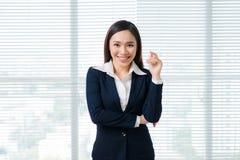 Portrait de sourire de femme d'affaires dans la fenêtre se tenante prêt de bureau Image stock