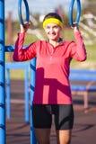 Portrait de sportive caucasienne positive dans l'équipement extérieur d'été ayant des exercices sur les anneaux photo stock