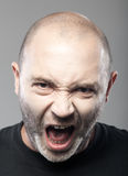 Portrait de sreaming fâché d'homme d'isolement sur le gris Images libres de droits