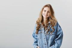 Portrait de studio d'amie blonde attirante heureuse avec des boucles, veste élégante de port de denim, tenant des mains dedans Photos stock