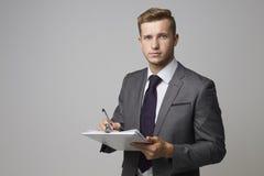 Portrait de studio d'homme d'affaires Writing On Clipboard Photographie stock