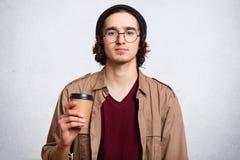 Portrait de studio d'homme sérieux avec la tasse de café aromatique chaud Type utilisant le chapeau noir élégant Concept de hippi photo stock