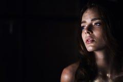Portrait de studio d'une belle fille avec de longs cheveux Scintillement sur votre visage Beaux yeux Fond foncé mystérieux images libres de droits