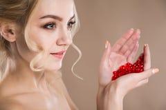 Portrait de studio d'une blonde dans ses capsules rouges de mains de vitamine Image stock