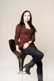 Portrait de studio d'une jolie jeune femme s'asseyant sur une chaise Photo stock