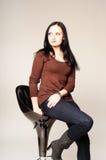Portrait de studio d'une jolie jeune femme s'asseyant sur une chaise Image libre de droits