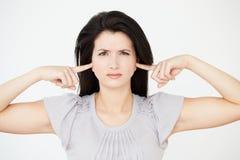Portrait de studio de femme avec des doigts dans des oreilles Photographie stock libre de droits