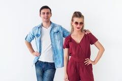 Portrait de studio de jeunes couples insouciants de sourire se tenant ensemble sur le fond blanc, homme étreignant tenant sa main Images stock
