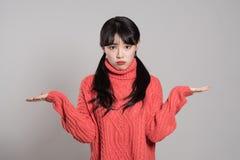 Portrait de studio de la femme 20 asiatique féminine an avec les deux mains dans la situation absurde images libres de droits