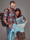 Portrait de studio des touristes masculins et féminins avec le sac à dos et la carte, se tenant dans un studio Photographie stock libre de droits