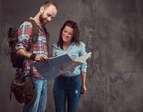Portrait de studio des touristes masculins et féminins avec le sac à dos et la carte, se tenant dans un studio Photos libres de droits