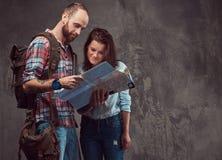 Portrait de studio des touristes masculins et féminins avec le sac à dos et la carte, se tenant dans un studio Photo stock