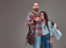 Portrait de studio des touristes masculins et féminins avec le sac à dos et la carte, se tenant dans un studio Photo libre de droits