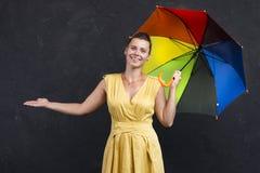Portrait de studio de jeune femme dans une robe avec un parapluie dans sa main Prévisions météorologiques image stock