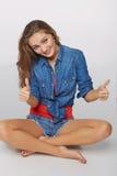 Portrait de style de denim de fille de l'adolescence sur le plancher donnant double thu Photographie stock