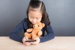 Portrait de téléphone intelligent d'une utilité asiatique de petite fille Photo stock