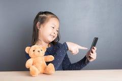 Portrait de téléphone intelligent d'une utilité asiatique de petite fille Photographie stock