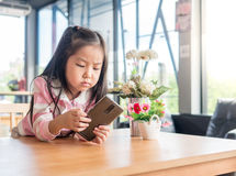 Portrait de téléphone portable de jeu de fille assez petite de l'Asie Photo stock
