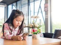 Portrait de téléphone portable de jeu de fille assez petite de l'Asie Image libre de droits