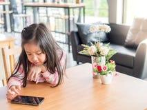Portrait de téléphone portable de jeu de fille assez petite de l'Asie Image stock