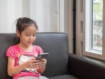 Portrait de téléphone portable de jeu de fille assez petite de l'Asie Photos libres de droits