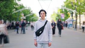 portrait de Temps-faute d'adolescent dans des écouteurs se tenant dehors dans la rue banque de vidéos